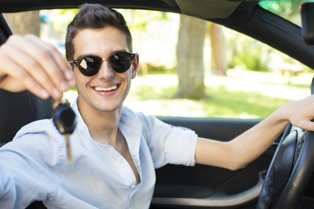 young man smiling in the car with the keys in hand